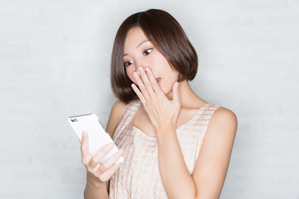 スマートフォンを見て驚く女性