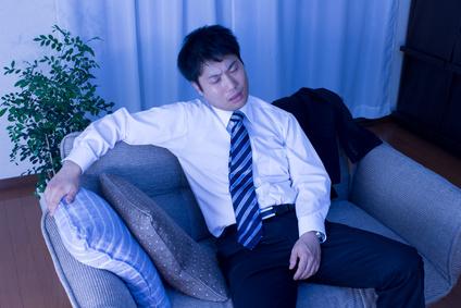 ソファーに腰をかける疲れたサラリーマン