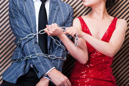 男性を鎖で拘束する女性