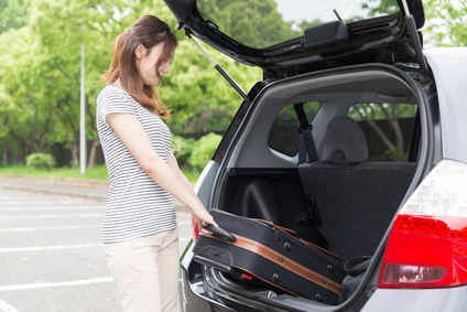 車のトランクからスーツケースを取り出す女性