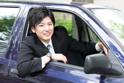 車の窓から顔を出す若手ビジネスマン