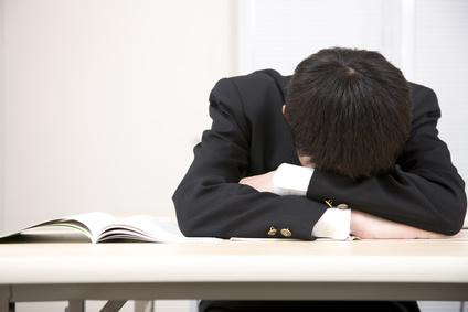 机に伏せ寝する中学生