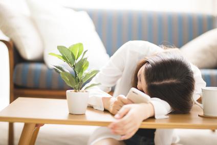 テーブルで伏せ寝する女性